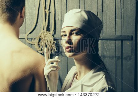 Sexy young couple of undressed male back and pretty nurse in white uniform wearing gloves near rope