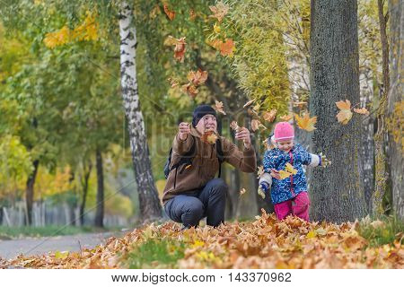 Happy father with little daughter are tossing up yellow autumn leaves in park outdoors