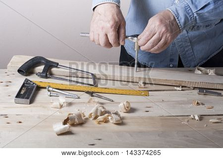 Carpenter working with plane on wooden background at Building Site. Joiner workplace.