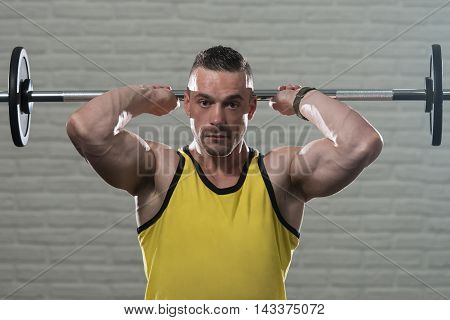 Young Man Working Out Triceps With Barbell On White Bricks Background With Copyspace poster