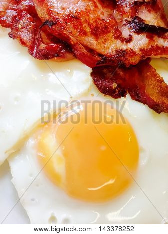 A sunny side up fried egg with crispy bacon