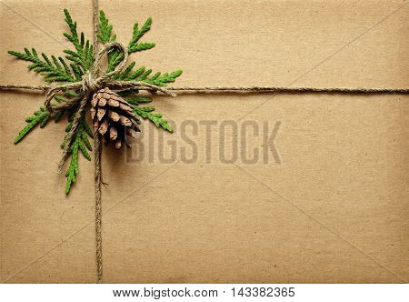 Brown cardboard tied box with green twigs cone and rope. Chrisrmas present.