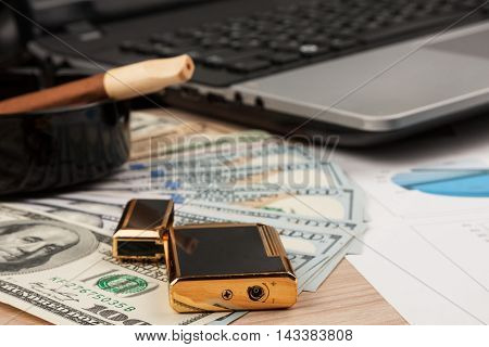 Working businessman desk Lighter and laptop cigar and money as the background