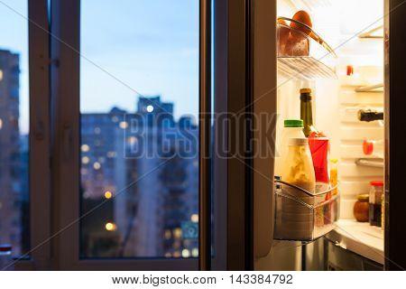 Open Door Of Refrigerator With Meal In Evening