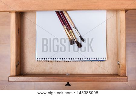 Paint Brushes On Drawing Album In Open Drawer