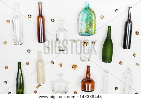 empty glass bottles and corks arranged on white background poster