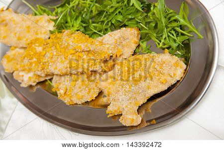 Meat with corn breadcrumbs on the silver plate