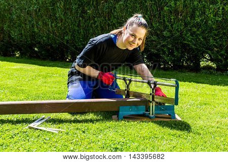 Girl Is Sawing A Wooden Beam In The Garden