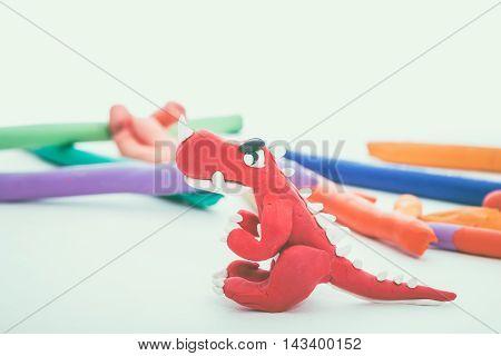 Creative Red Dinosaur Clay Model. Play Dough Animal. Vintage Tone Effect.