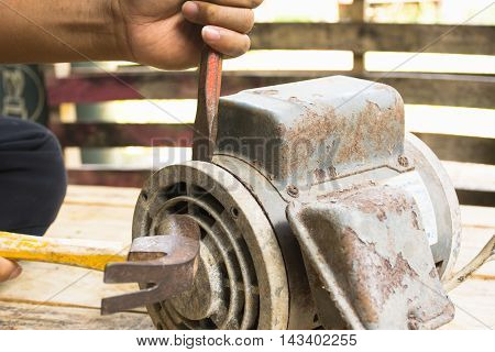 Old electric motor  and man working equipment repair on wooden floor background.Background craftsman or equipment.Zoom in