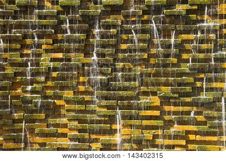 Stone walls and water.Waterfall stone wall and flat rocks.