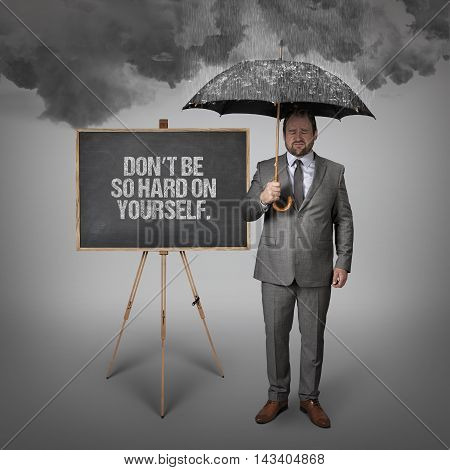 Dont be so hard on yourself text on blackboard with businessman holding umbrella