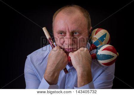 Portrait of sad musician with Ukrainian woodwind instrument sopilka and maracas