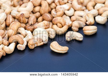 Roasted pile of cashew nuts on black plate