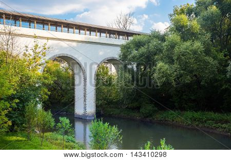White aqueduct bridge across Yauza river with trees