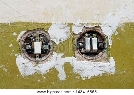 Two old electric switches mounted in the wall. The covers of switches is open.
