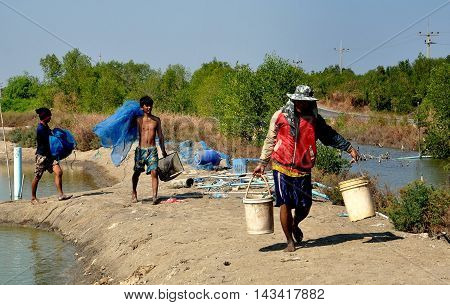 Samut Songkhram Thailand - December 29 2011: Thai fishermen carrying buckets and nets heading for lunch after working the ponds at a local fish farm