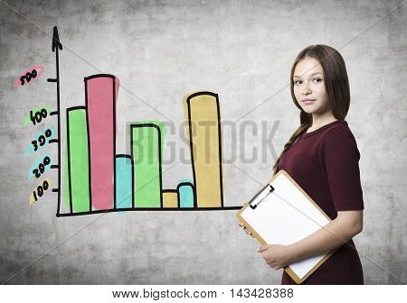 Youn waman with a clipboard is standing near concrete wall with bar chart on it. Concept of business counseling.