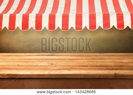 Empty wooden counter background with red stripes awning