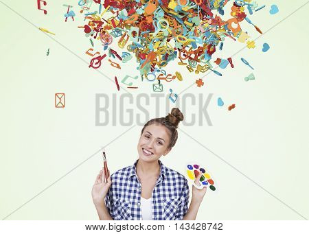 Girl with palette and paintbrush standing in room with smal social media icon bunch above her head. Concept of dreaming. Green background.