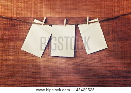 Vintage cards hanging on string over wooden background. Place for your text