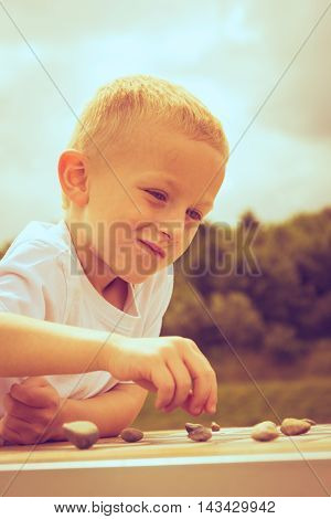 Draughts board game. Little boy clever child kid playing checkers thinking outdoor in the park. Childhood and development