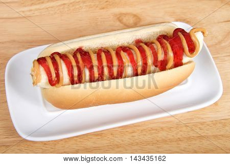 Banana with peanut butter and jelly in a hot dog bun served on a white rectangular plate served on a wood table. Top view from an angle