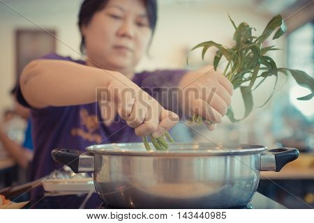 Asia Woman Cooking By Put A Vegetable In To A Hot Pot