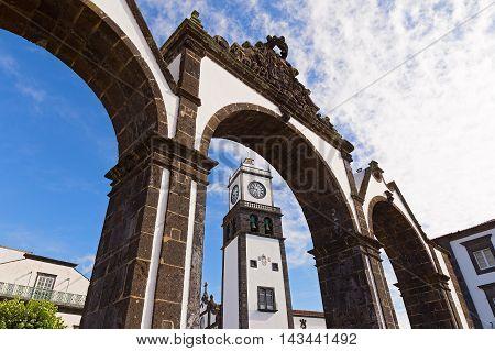 The historical entrance (Portas da Cidade) to the village of Ponta Delgada in Azores Portugal. Entrance gates and the clock tower of Saint Sabastian church.