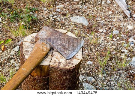 Photo of old blunt axe on log