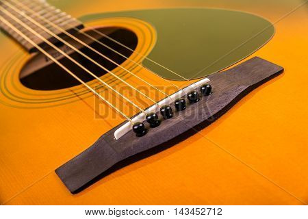 Close up background of classic acoustic guitar showing the origin of the strings from the bridge