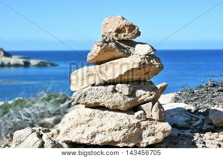 Stone stack or stack rock of pebbles at a high coast with copy space. Balanced stones.