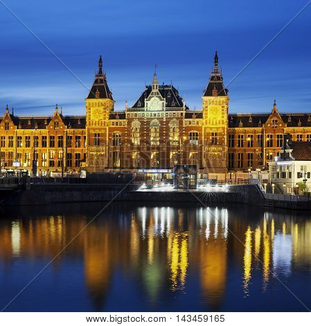 Night city view of Amsterdam canal and Centraal Station Holland Netherlands
