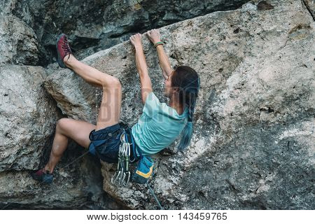Sporty young woman in safety harness with outfit started to climbing the rock wall outdoor