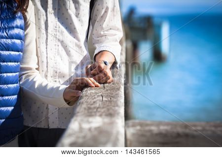 Hands of young couple near together at old pier railing by the sea