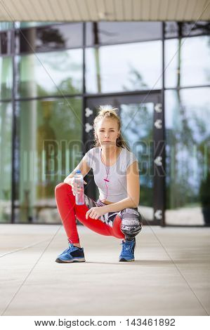 Fit and beautiful blonde urban woman in sportswear taking a break after workout. Rests in city environment in tights and crop top.