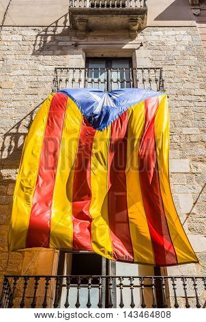 Flag Of Catalonia Waving In The Downtown Of Girona. Spain.