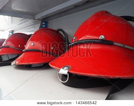 Red fireman helmet prepared on shelf for fireman.