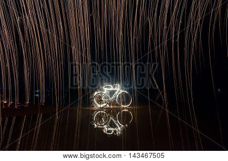 swing steel wool fire on a bike and sea water reflection