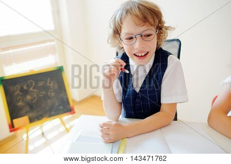 Cheerful little student bespectacled sits at school desk. It is a disciple of an elementary school. In a hand at boy ball pen. On a school desk copybooks lay. Near to a school desk a small blackboard.