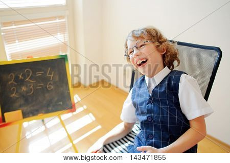 Funny little schoolboy in glasses cheerfully laughs. This elementary school student. Nearby is a small blackboard. Back to school.