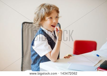 Cute little schoolboy sitting at a school desk with dreaming views. A boy looking somewhere to the side. On a school desk there are school accessories and copybooks. This elementary school student.