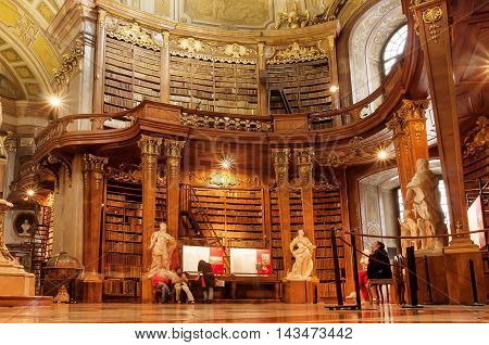 VIENNA, AUSTRIA - MAY 30, 2016: People relaxing inside the Austrian National Library with old luxury furniture on May 30, 2016. Est in 18th century the largest library in Austria with 7.4 mill items