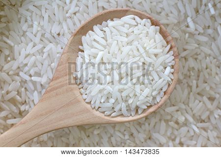 Organic jasmine rice in wooden spoon on pile grain rice for nature food background.