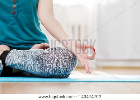 Yoga meditation in light room, woman sitting lotus position, hands closeup