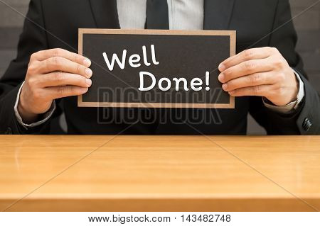 Well done. word writing on black banner and holding by businessman