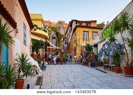 ATHENS, GREECE - AUGUST 20, 2016: People in a coffee shop in the old town of Plaka under Acropolis, Athens on August 20, 2016.