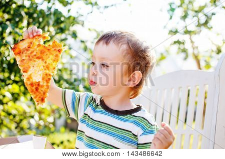 kid enjoying pizza outdoors. boy holding a slice of pizza aweigh and intending to bite off