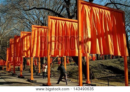 New York City - February 13 2005: Man photographs his wife and child under the orange panels of Christo's art installation The Gates in Central Park