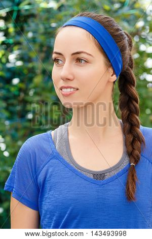Portrait of smiling sporty brunette woman in blue sportswear outdoor. Fit sporty and athletic young woman. Beautiful girl in a sportswear. Hairstyle for sports. Healthy stylish sporty girl posing